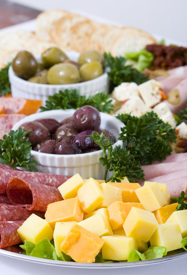 Antipasto catering platter. An antipasto catering platter of continental meats and feta cheese over a bed of mixed greens plus marinated artichoke hearts, olives stock images