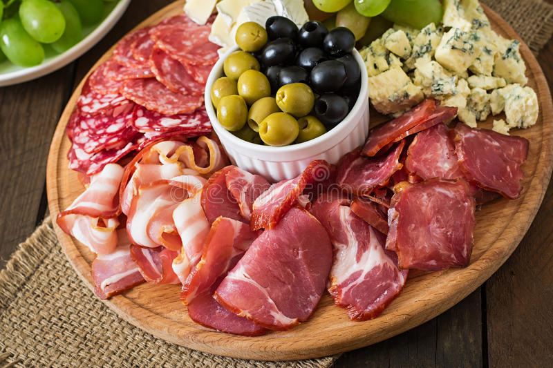 Antipasto catering platter with bacon, jerky, salami, cheese and grapes. On a wooden background stock images
