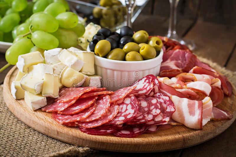 Antipasto catering platter with bacon, jerky, salami, cheese and grapes. On a wooden background royalty free stock photos