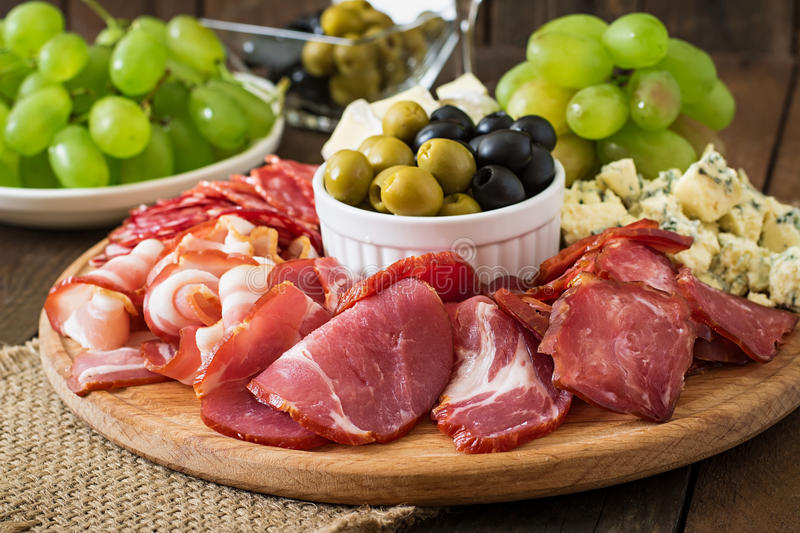 Antipasto catering platter with bacon, jerky, salami, cheese and grapes. On a wooden background stock photo