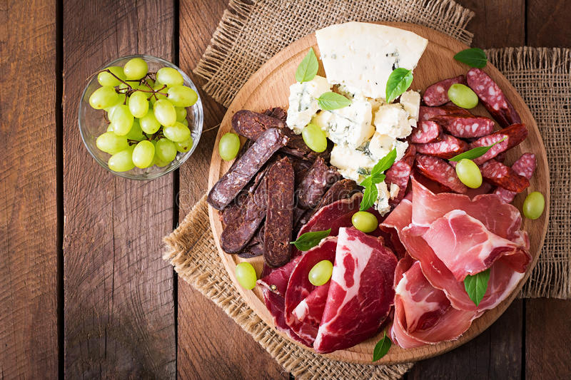 Antipasto catering platter with bacon, jerky, sausage, blue cheese and grapes. On a wooden background royalty free stock image