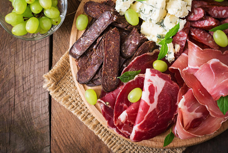 Antipasto catering platter with bacon, jerky, sausage, blue cheese and grapes. On a wooden background royalty free stock photos