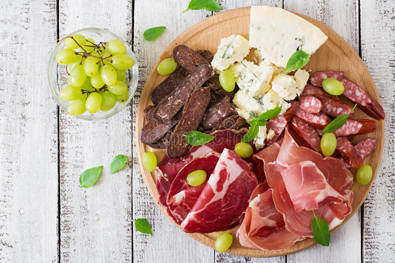 Antipasto catering platter with bacon, jerky, sausage, blue cheese and grapes. On a wooden background. Top view royalty free stock photo