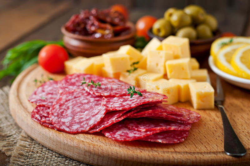 Antipasto catering platter with salami and cheese. On a wooden background royalty free stock photography