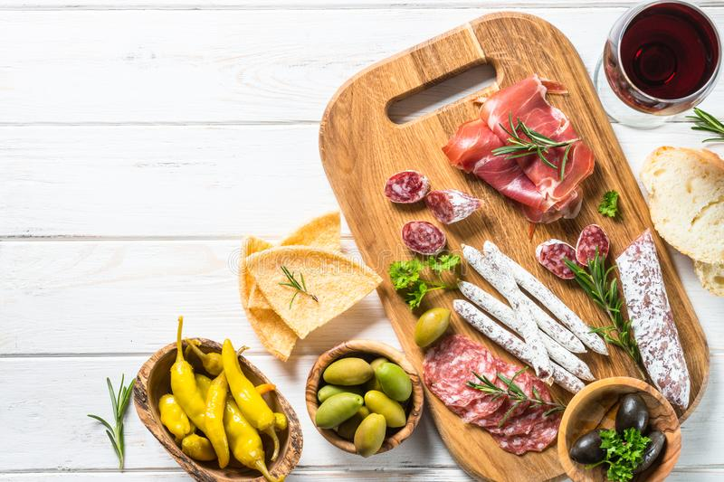 Antipasto delicatessen - meat, cheese and olives. Antipasto delicatessen - sliced meat, ham, salami, cheese, olives, ciabatta and pepperoni on white. Top view stock images