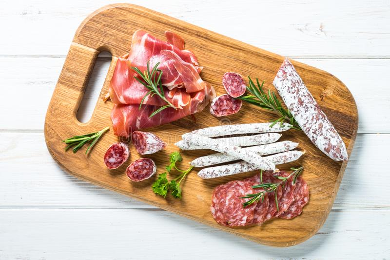 Antipasto delicatessen - meat, cheese and olives. Antipasto delicatessen - sliced meat, ham, salami, cheese, olives, ciabatta and pepperoni on white. Top view royalty free stock photo