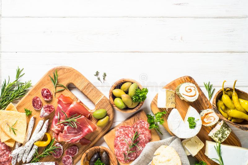 Antipasto delicatessen - meat, cheese and olives. Antipasto delicatessen - sliced meat, ham, salami, cheese, olives, ciabatta and pepperoni on white wooden royalty free stock photos