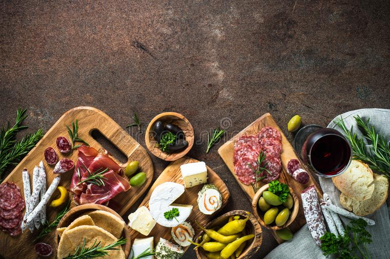 Antipasto delicatessen - meat, cheese, olives and wine on stone. Antipasto delicatessen - sliced meat, ham, salami, cheese, olives, ciabatta and red wine on dark royalty free stock images