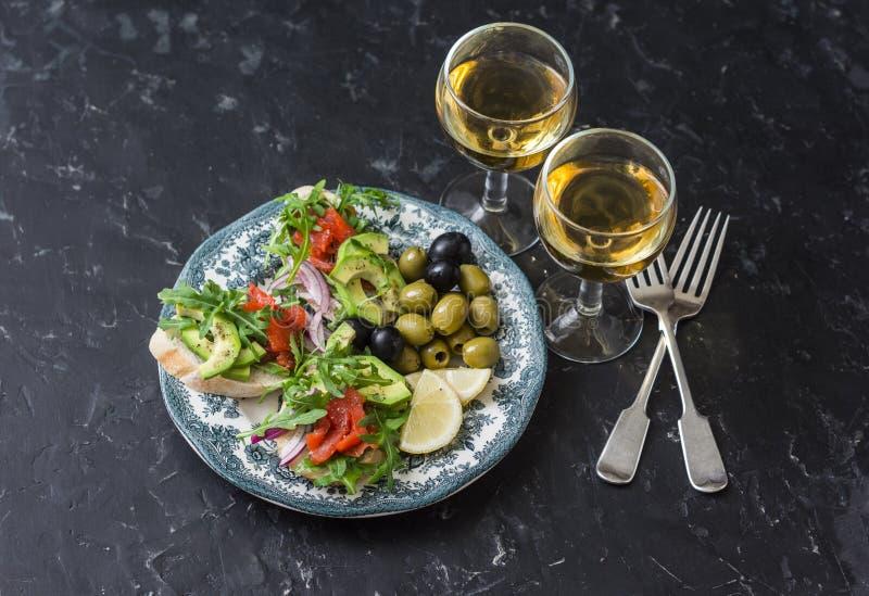Antipasto et vin méditerranéens de style Saumons fumés, avocat, bruschette d'arugula, olives et deux verres de vin blanc photo stock