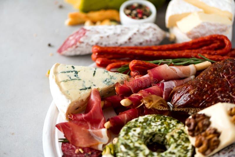 Antipasto italiano tradicional, tabla de cortar con el salami, carne ahumada fría, prosciutto, jamón, quesos, aceitunas, alcaparr imágenes de archivo libres de regalías