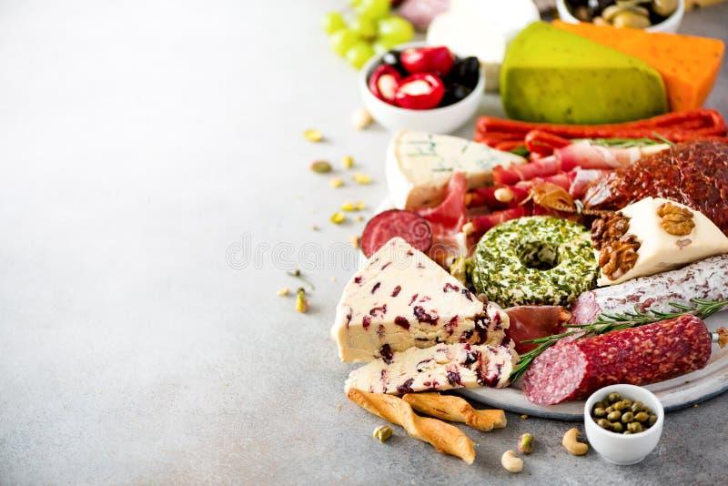 Antipasto italiano tradizionale, tagliere con salame, carne affumicata fredda, prosciutto di Parma, prosciutto, formaggi, olive,  fotografia stock libera da diritti