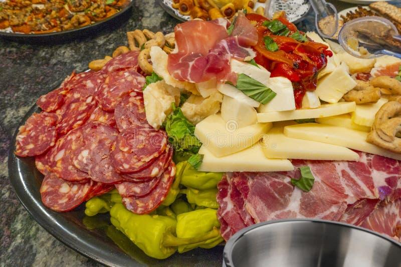 Antipasto jedzenie na stalowym tacy plater z serami Prosciutto, Provolone, Sopressata, Manchego, bejcujący pieprze gotujący piepr zdjęcia royalty free