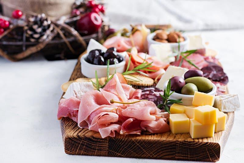Antipasto met ham, prosciutto, salami, kaas, kraakbeen en olijven op een lichte achtergrond stock afbeeldingen