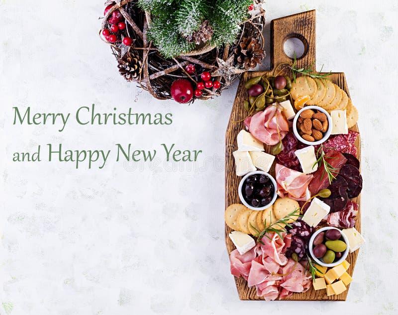 Antipasto met ham, prosciutto, salami, kaas, kraakbeen en olijven op een lichte achtergrond Kersttafel royalty-vrije stock fotografie