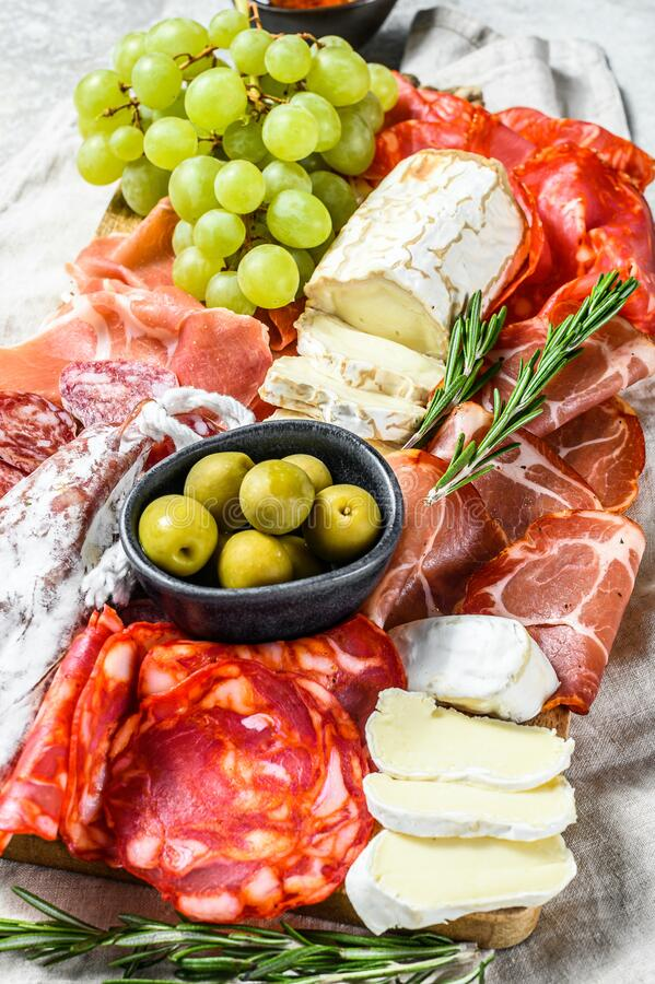 Antipasto platter cold meat with grapes, prosciutto, slices ham, beef jerky, chorizo salami, fuet, Camembert and goat cheese. Gray royalty free stock photography