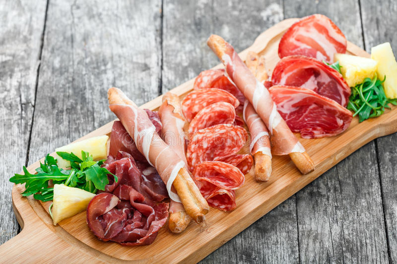 Antipasto platter cold meat plate with grissini bread sticks, prosciutto, slices ham, beef jerky, salami and arugula on board stock photography