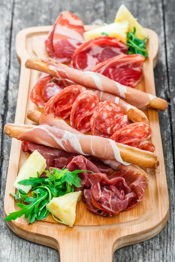Antipasto platter cold meat plate with grissini bread sticks, prosciutto, slices ham, beef jerky, salami on cutting board stock images