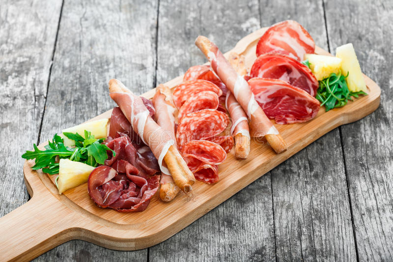 Antipasto platter cold meat plate with grissini bread sticks, prosciutto, slices ham, beef jerky, salami on cutting board. Antipasto platter cold meat plate with royalty free stock image