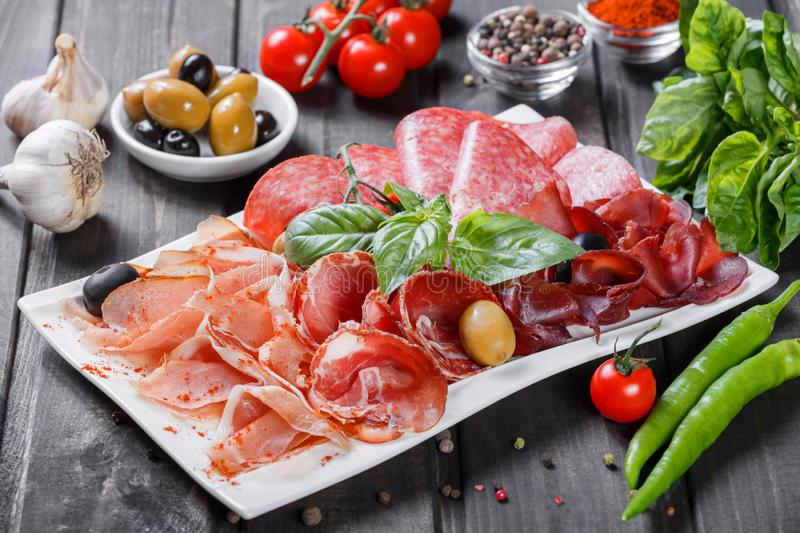 Antipasto platter cold meat plate with prosciutto, slices ham, salami, decorated with basil and olive. On wooden background. Meat appetizer. Top view royalty free stock photos