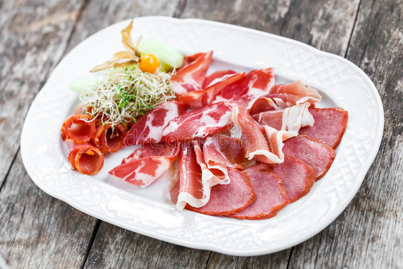 Antipasto platter cold meat plate with prosciutto, slices ham, salami, decorated with physalis and slices of melon. On wooden background. Meat appetizer. Top stock image