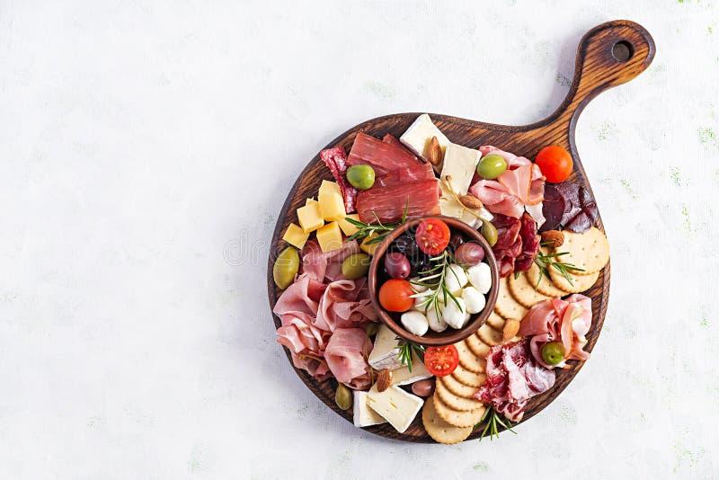 Antipasto platter com presunto, presunto, salame, queijo, bolachas e azeitonas num fundo leve fotos de stock royalty free