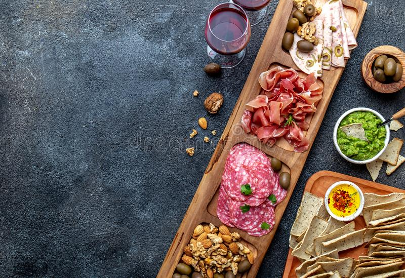 Antipasto Platter. Ham serrano, salami olive jamon dip sauces and red wine. Top view stock photo
