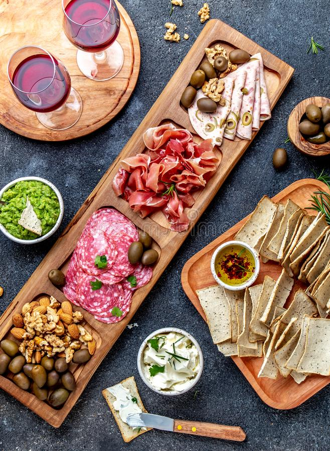 Antipasto Platter. Ham serrano, salami olive jamon dip sauces and red wine. Top view royalty free stock images