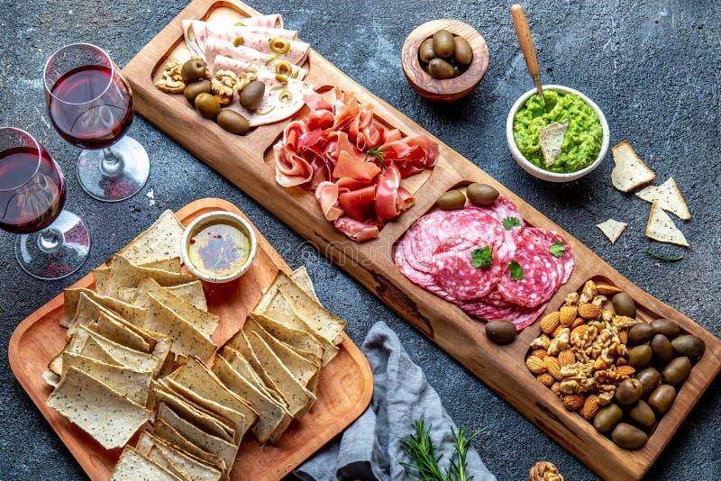 Antipasto Platter. Ham serrano, salami olive jamon dip sauces and red wine. Top view stock image