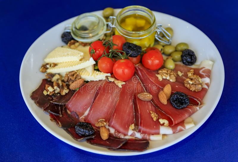 Antipasto platter with the Montenegrin Njeguski prsut prosciutto and cheese in Budva Montenegro. Antipasto plate of Njeguski prsut cured meat, cheese, olive oil stock photo