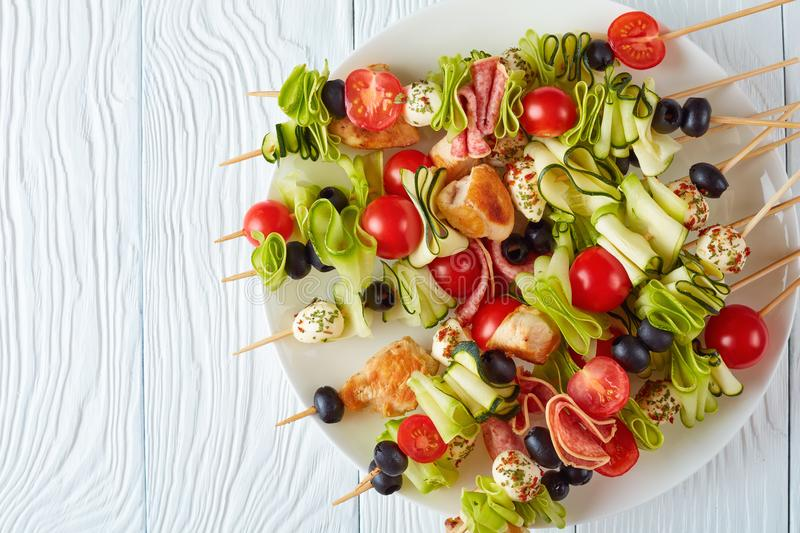 Antipasto skewers with meat and veggies. Antipasto skewers with grilled chicken meat, raw zucchini ribbons, tomatoes, seasoned mozzarella balls, salami slices stock photography