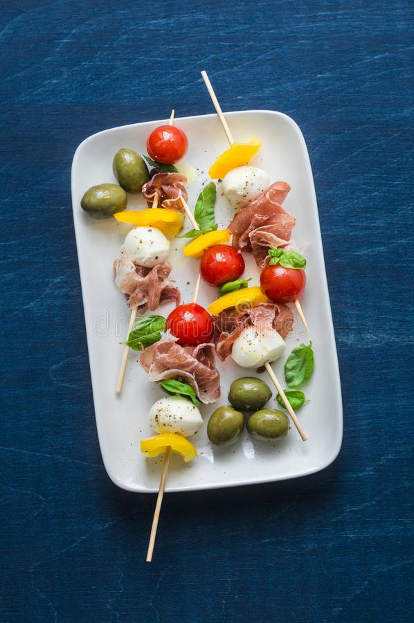 Antipasto skewers. Mediterranean appetizer to wine - prosciutto, bell peppers, cherry tomatoes, mozzarella cheese on skewers. Deli stock images