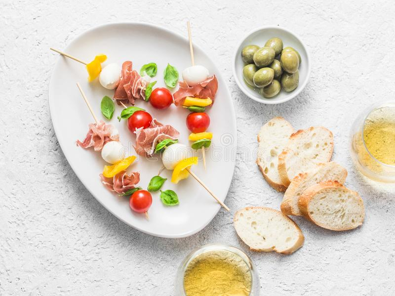 Antipasto skewers. Mediterranean appetizer to wine - prosciutto, bell peppers, cherry tomatoes, mozzarella cheese on skewers and w. Hite wine. Delicious snack royalty free stock image