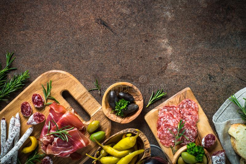Antipasto - sliced meat, ham, salami, olives on dark stone table. Top view with space for text stock images