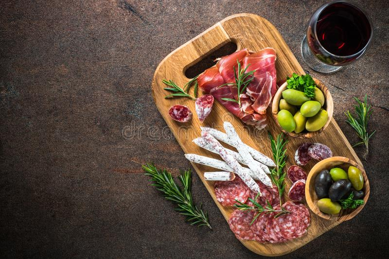 Antipasto - sliced meat, ham, salami, olives and wine top view. Antipasto - sliced meat, ham, salami, olives and glass wine on dark stone table. Top view with royalty free stock photos