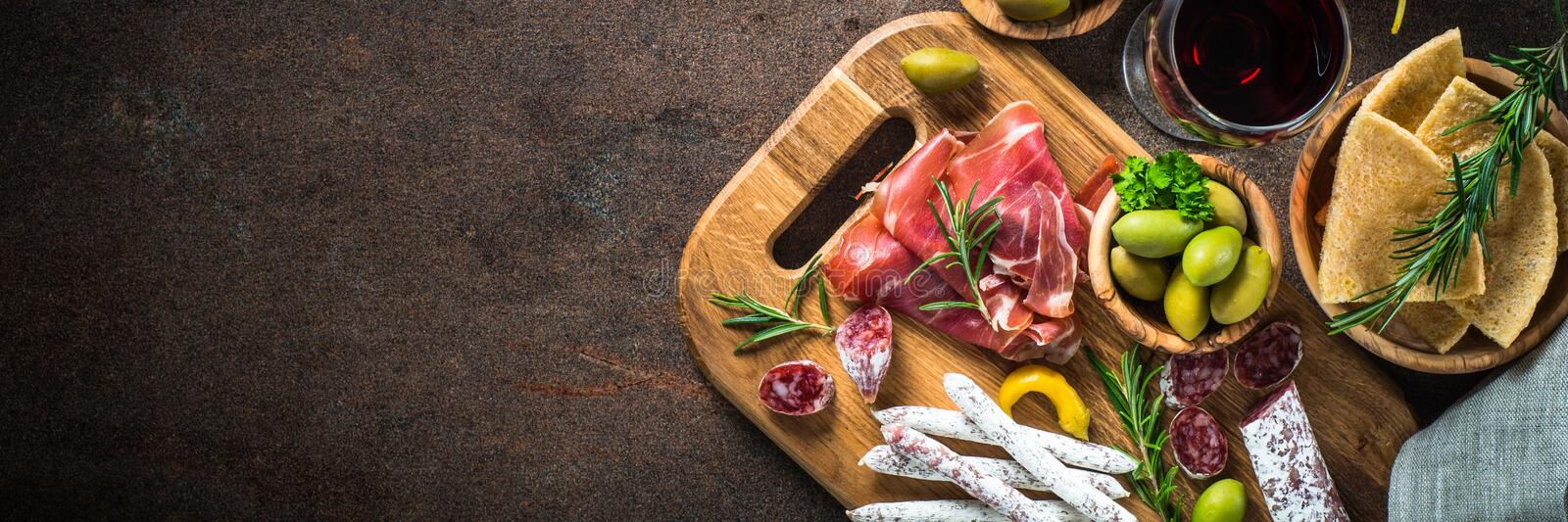 Antipasto - sliced meat, ham, salami, olives and wine top view. Antipasto - sliced meat, ham, salami, olives and glass wine on dark stone table. Top view long royalty free stock image