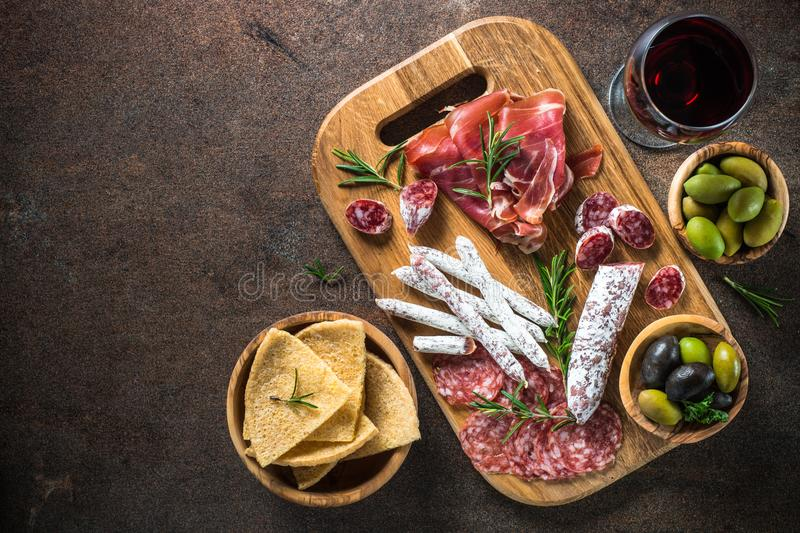Antipasto - sliced meat, ham, salami, olives and wine top view. Antipasto - sliced meat, ham, salami, olives and glass wine on dark stone table. Top view with stock photos