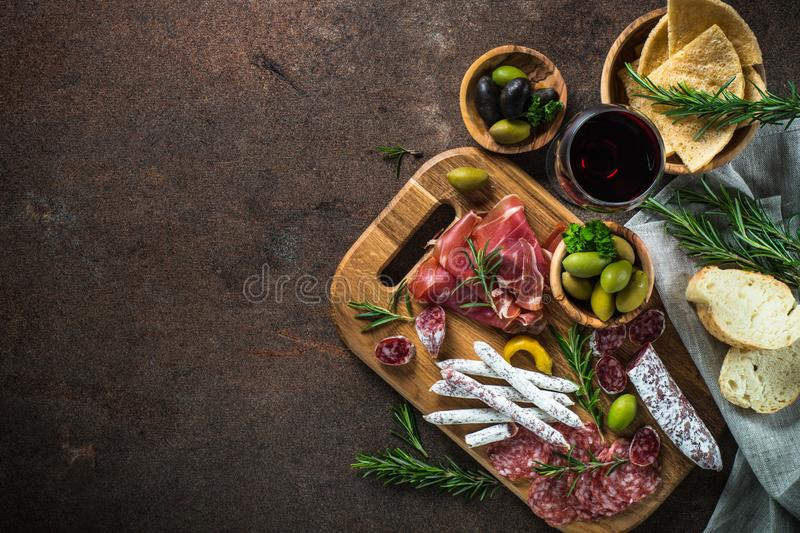 Antipasto - sliced meat, ham, salami, olives and wine top view. Antipasto - sliced meat, ham, salami, olives and glass wine on dark stone table. Top view with stock image