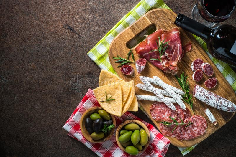 Antipasto - sliced meat, ham, salami, olives and wine  top view. Antipasto - sliced meat, ham, salami, olives and glass wine on dark stone table. Top view with royalty free stock image
