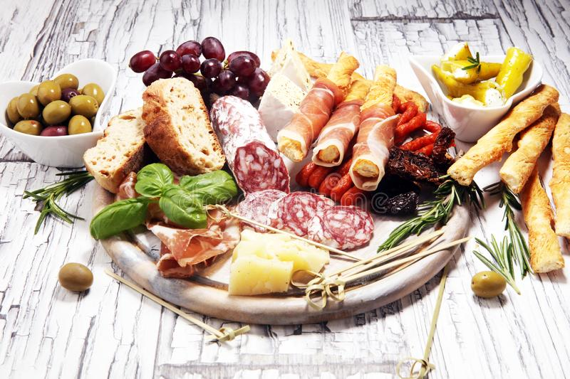 Antipasto various appetizer. Cutting board with prosciutto, salami, cheese, bread and olives on white wooden background stock photos