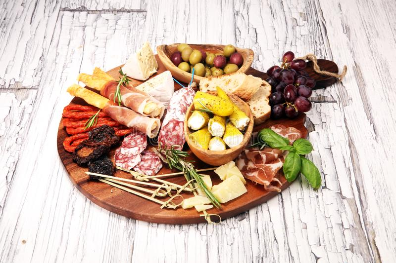 Antipasto various appetizer. Cutting board with prosciutto, salami, cheese, bread and olives on white wooden background stock images