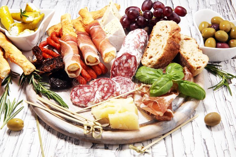 Antipasto various appetizer. Cutting board with prosciutto, salami, cheese, bread and olives on white wooden background stock photo