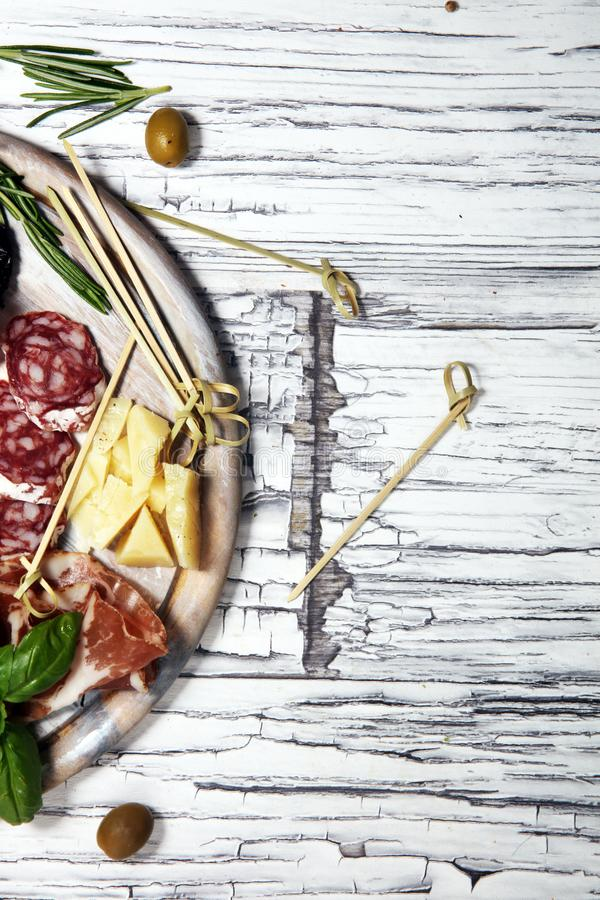 Antipasto various appetizer. Cutting board with prosciutto, salami, cheese, bread and olives on white wooden background stock photography