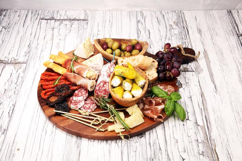 Antipasto various appetizer. Cutting board with prosciutto, salami, cheese, bread and olives on white wooden background royalty free stock images