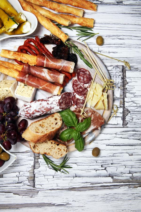 Antipasto various appetizer. Cutting board with prosciutto, salami, cheese, bread and olives on white wooden background stock image