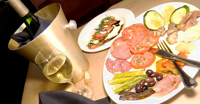 Antipasto and Wine. Fine Italian Dining with an Antipasto Platter a Caprese Salad and White Wine royalty free stock image