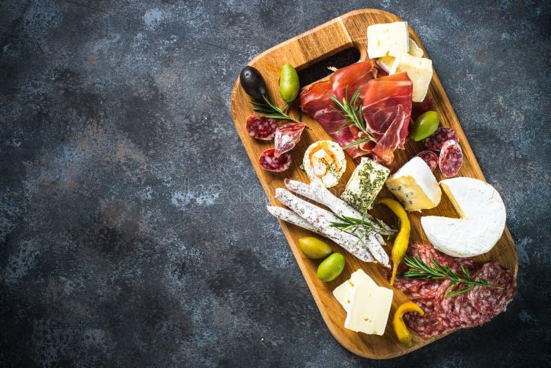 Antipastobräde med skivat kött, skinka, salami, ost, oliv och rött vin fotografering för bildbyråer