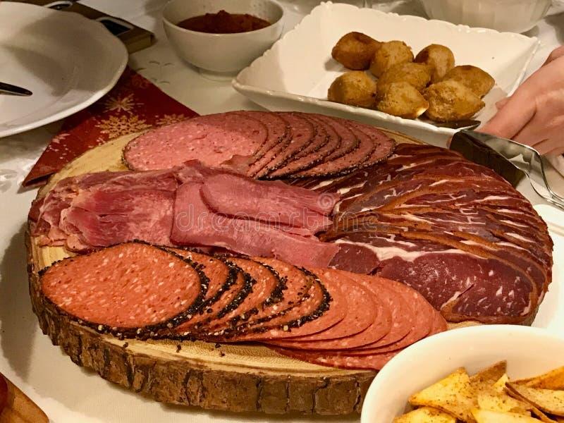 Antipastodelikatessen - geschnittenes Fleisch, Schinken, Salami, Pastrami/pastirma und Rinderzungescheiben auf hölzernem Brett stockbild
