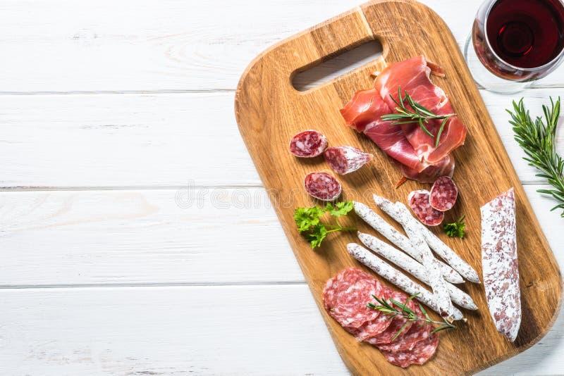 Antipastomatvaruaffär - kött, skinka och vin på vit arkivfoto
