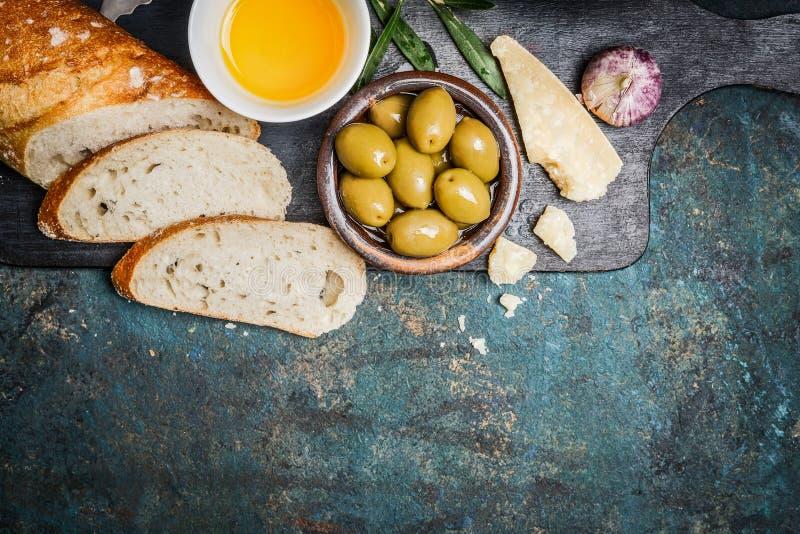Antipastysnack met gesneden ciabattabrood, olijven, olie, knoflook en parmezaanse kaaskaas op donkere scherpe raad op rustieke ac royalty-vrije stock afbeelding