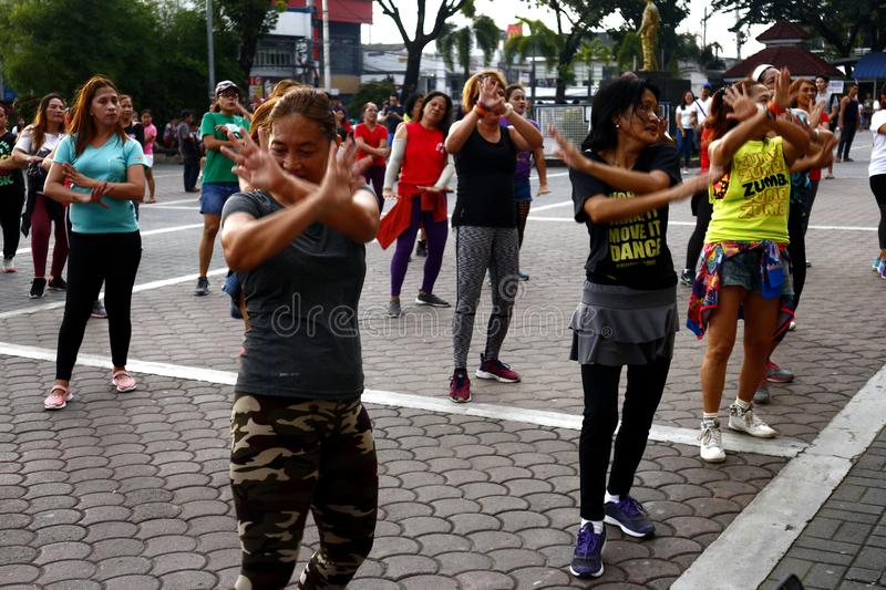 Adult Filipino ladies participate in a Zumba or dance exercise class at a public park. ANTIPOLO CITY, PHILIPPINES – AUGUST 12, 2019: Adult Filipino ladies stock images